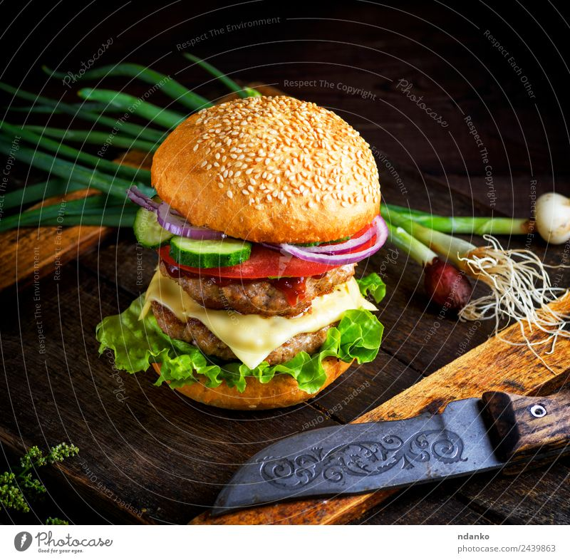 double cheeseburger with vegetables Meat Cheese Vegetable Bread Roll Lunch Fast food Knives Table Restaurant Wood Eating Fresh Large Delicious Green Red Black