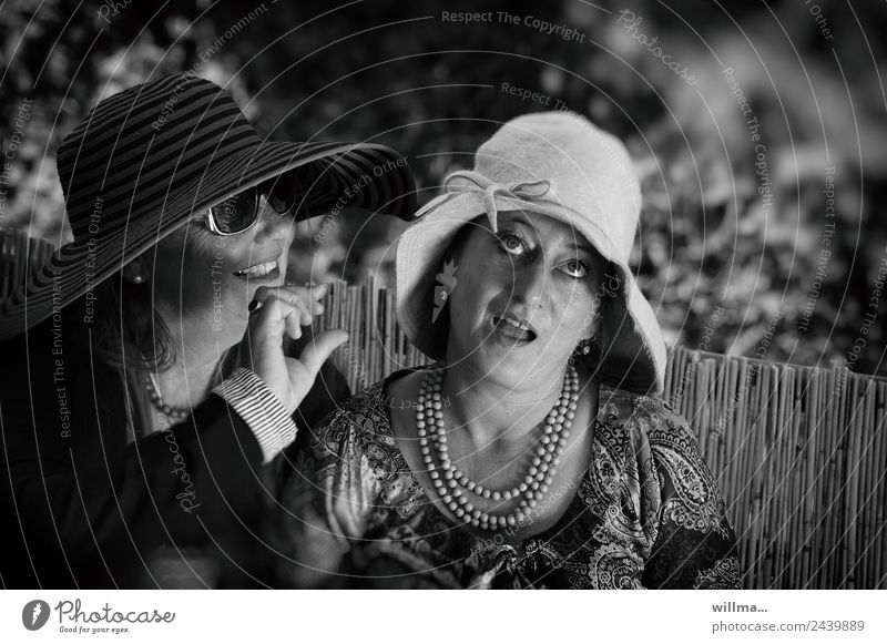 Two ladies in hats obviously gossiping about the size of the man Woman Lady 2 Gossip talk Jewellery Sunglasses Necklace Hat Upward Communicate queer wittily