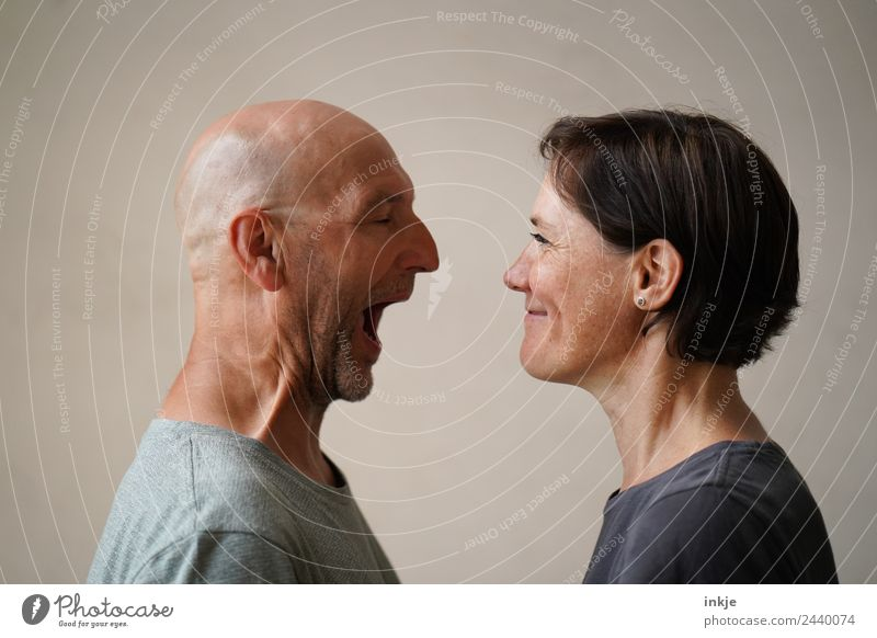 Man and woman face each other. The man opens his mouth wide, the woman grins. Lifestyle Leisure and hobbies Woman Adults Friendship Couple Partner Face 2