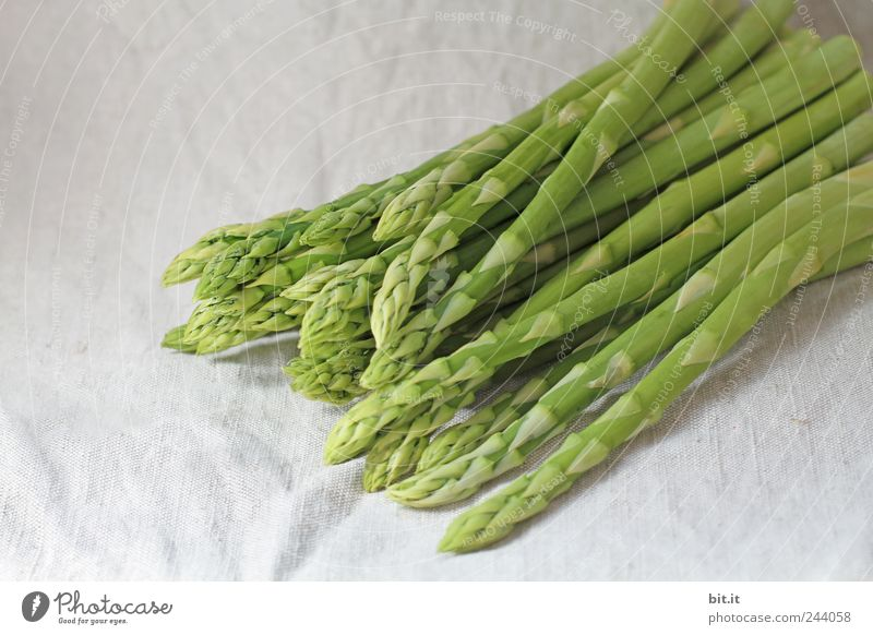 Portion of asparagus bunch with green, fresh, juicy asparagus, from fresh, local harvest, lies in heaps, bundles on a white cloth made of linen. Food Vegetable