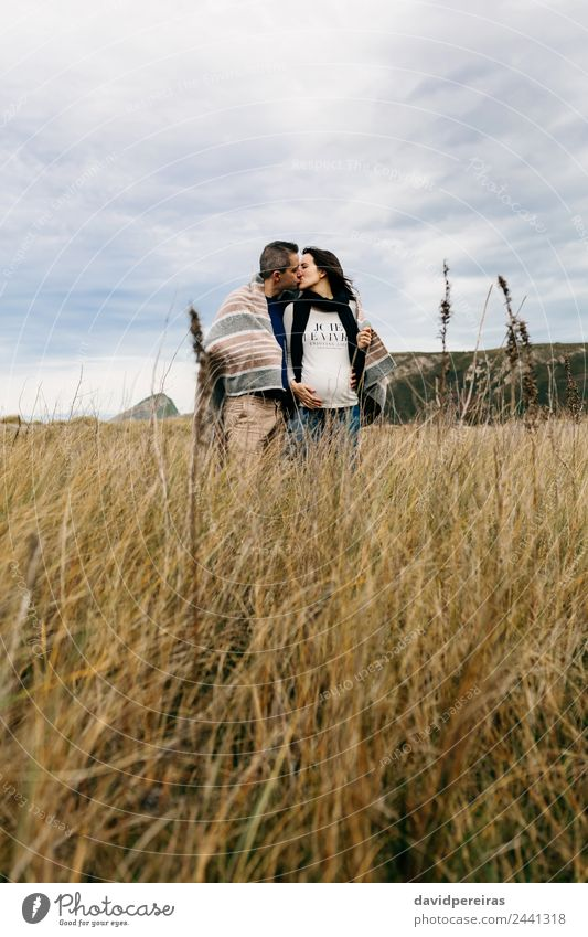 Couple kissing on the field Lifestyle Calm Leisure and hobbies Winter Woman Adults Man Parents Family & Relations Nature Landscape Clouds Autumn Grass Scarf