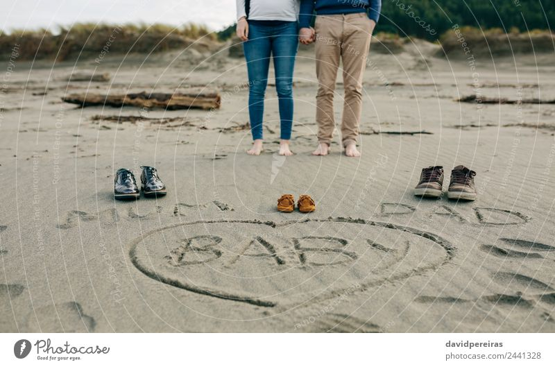 Mum, dad and baby written on the sand with the parents behind Woman Human being Man Winter Beach Adults Lifestyle Autumn Love Funny Family & Relations Feet