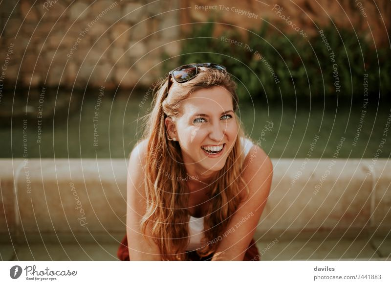 Young blonde woman portrait laughing outdoors sitting in a garden, and looking at camera. Joy Beautiful Face Human being Young woman Youth (Young adults) Woman