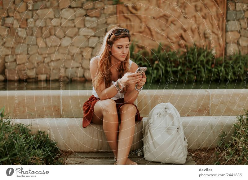 Blonde chic girl using a smart phone outdoors Lifestyle Beautiful Garden Telephone PDA Internet Human being Young woman Youth (Young adults) Woman Adults 1