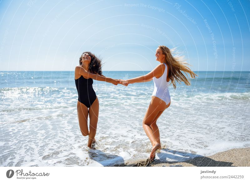 Two women with their hands caught on the beach Lifestyle Joy Leisure and hobbies Vacation & Travel Summer Beach Human being Feminine Young woman