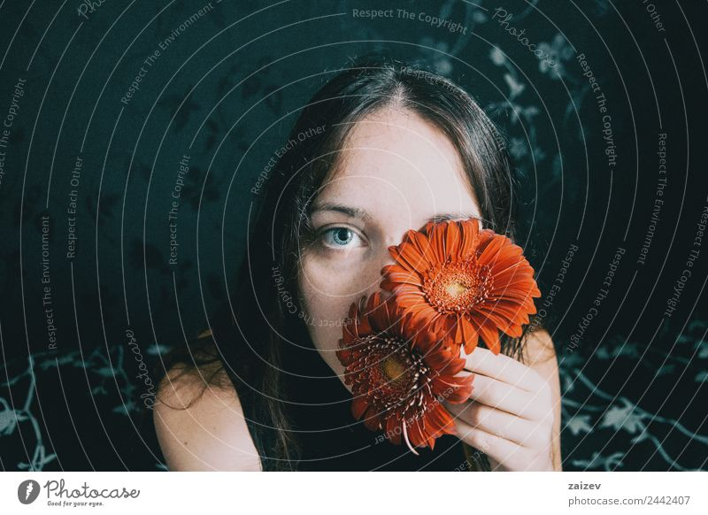 a girl with blue eyes and long hair covering herself with a gerbera flower Lifestyle Beautiful Face Relaxation Calm Human being Woman Adults Plant Flower