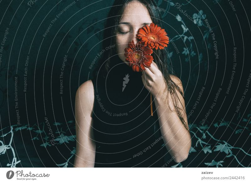 a girl with blue eyes and long hair covering herself with a gerbera flower Lifestyle Elegant Beautiful Face Relaxation Calm Human being Feminine Young woman