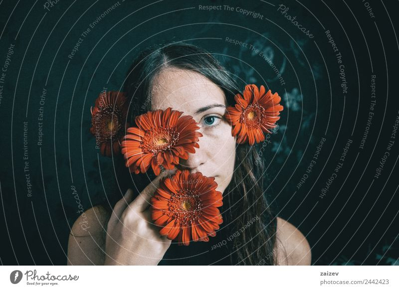 a girl with blue eyes and long hair covering herself with a gerbera flower Lifestyle Beautiful Face Relaxation Calm Human being Feminine Young woman