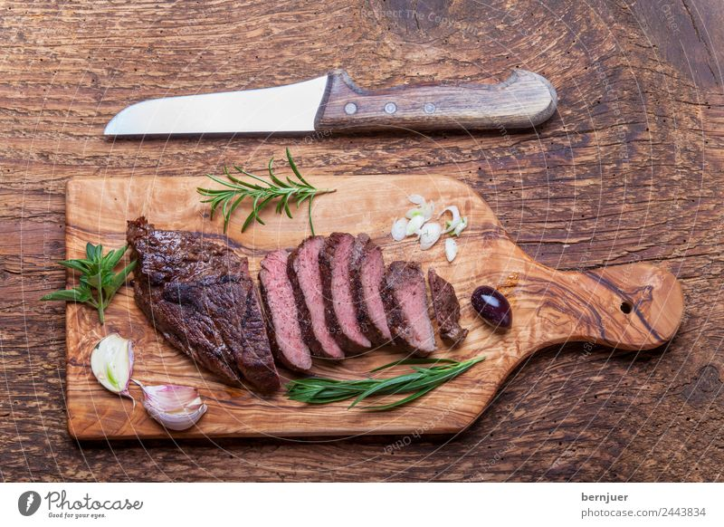 Slices of a grilled steak on wood Food Meat Herbs and spices Media Barbecue (apparatus) Wood Authentic Steak Beef board Knives Blade boil BBQ Ribeye supervision