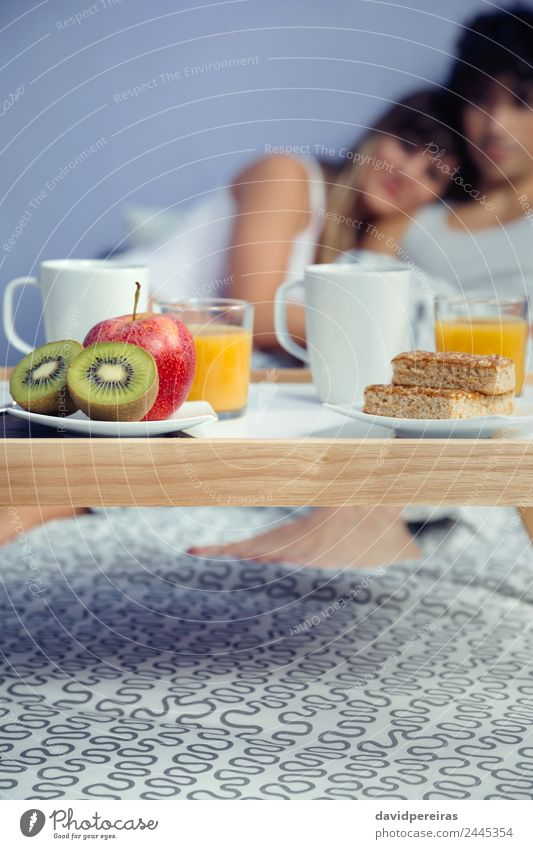 Healthy breakfast on tray and couple lying in background Fruit Apple Breakfast Juice Coffee Lifestyle Happy Beautiful Relaxation Leisure and hobbies Bedroom