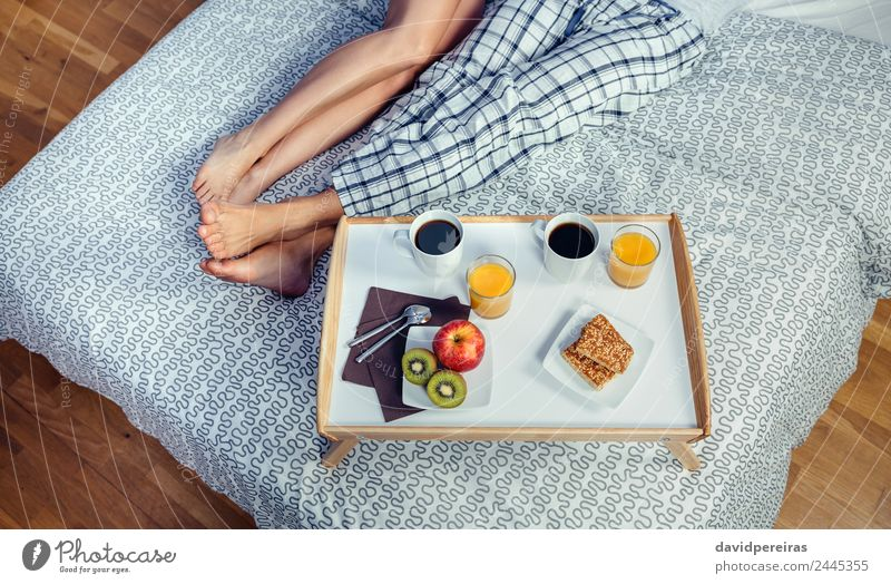 Healthy breakfast on tray and couple legs over bed Fruit Apple Breakfast Juice Coffee Lifestyle Happy Relaxation Leisure and hobbies Bedroom Woman Adults Man