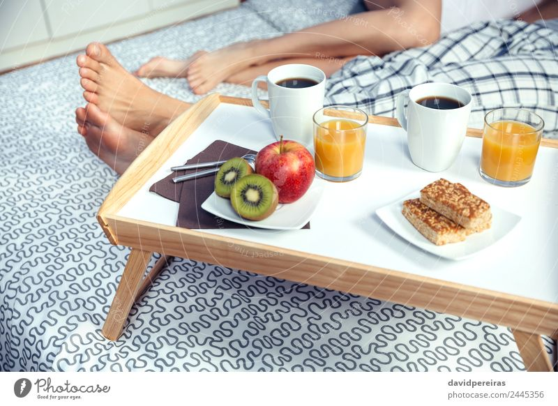 Healthy breakfast on tray and couple legs in background Fruit Apple Breakfast Juice Coffee Lifestyle Happy Relaxation Leisure and hobbies Bedroom Woman Adults