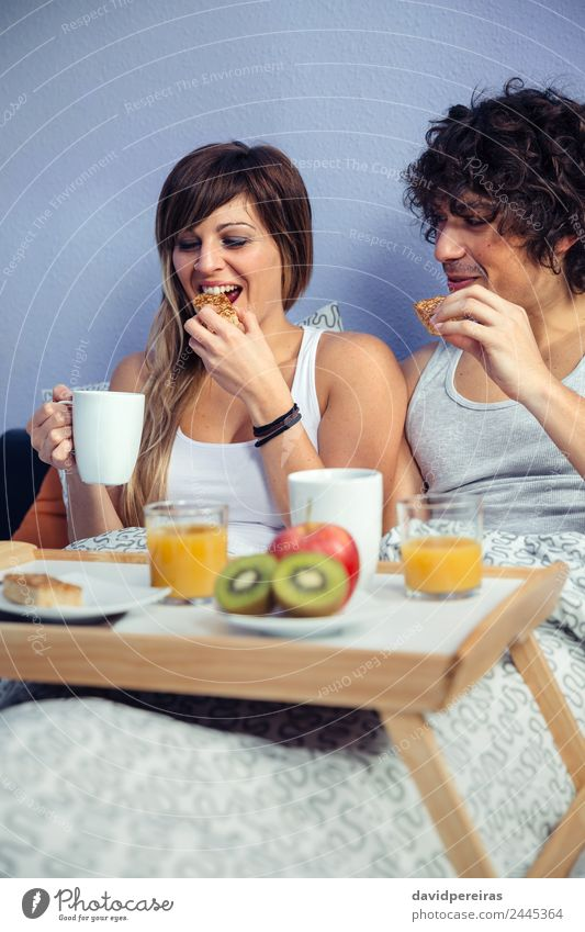 Couple having breakfast in bed served over tray Fruit Apple Breakfast Juice Coffee Lifestyle Happy Beautiful Relaxation Leisure and hobbies Bedroom Woman Adults