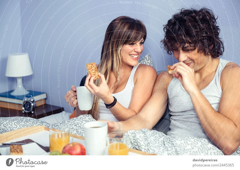 Couple laughing and having breakfast in bed at home Fruit Apple Breakfast Juice Coffee Lifestyle Happy Beautiful Relaxation Leisure and hobbies Bedroom Woman
