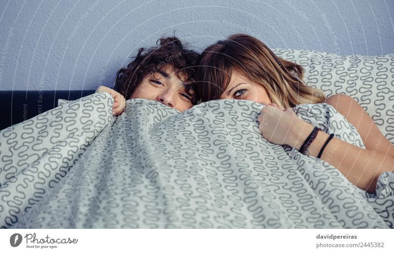 Happy couple laughing and covering mouths under duvet Lifestyle Beautiful Relaxation Bedroom Camera Woman Adults Man Couple Mouth Smiling Laughter Love