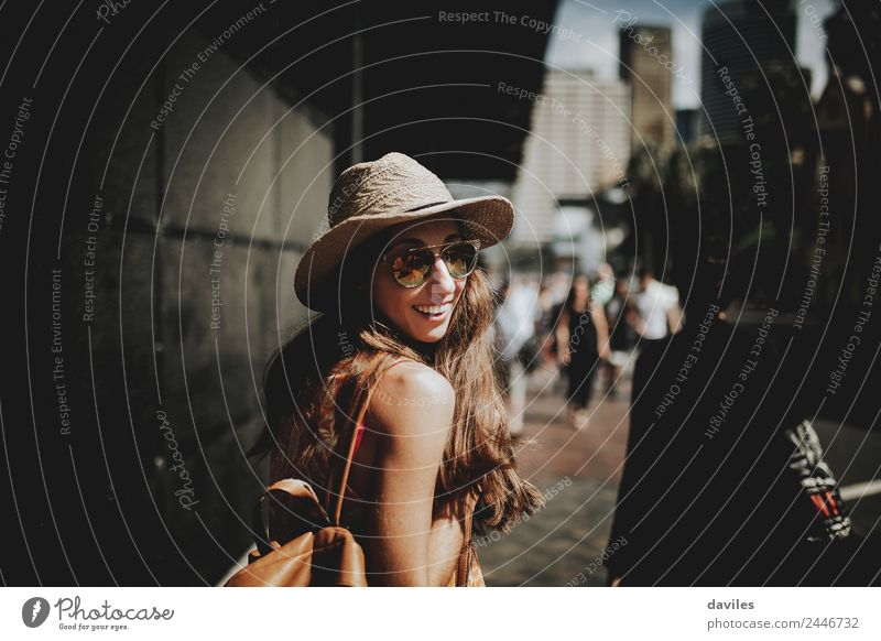 Happy woman in sunglasses and hat walking by Sydney city streets, and looking back to the camera. Lifestyle Shopping Style Leisure and hobbies Vacation & Travel