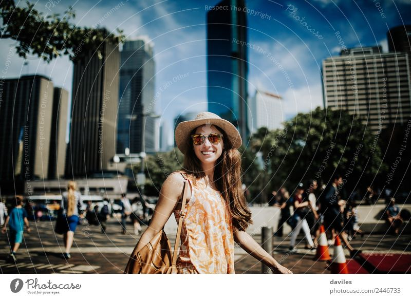 Cute smiling woman with hat and sunglasses walking in the street with Sydney cityscape in the background. Lifestyle Shopping Style Joy Beautiful