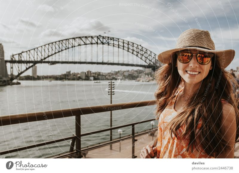 Smiling girl with hat and sunglasses posing with Harbour Bridge in the background, in Sydney, Australia. Lifestyle Style Joy Happy Vacation & Travel Trip