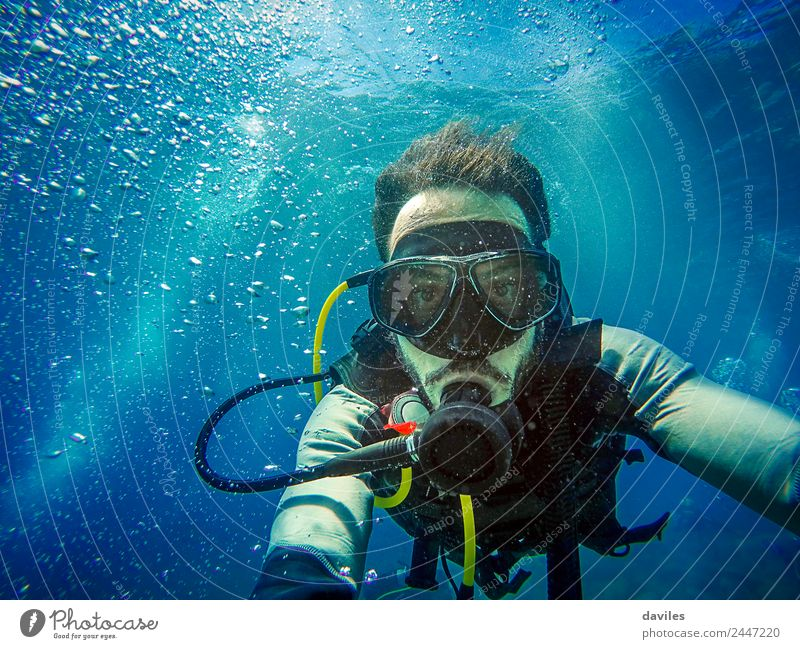 Man with scuba diving equipment diving in the sea and looking at camera with blue water background. Lifestyle Exotic Joy Leisure and hobbies Vacation & Travel
