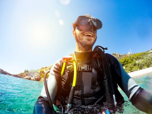 Happy man wearing diving clothes and equipment, smiling while get out of the water in the beach. Lifestyle Joy Face Relaxation Leisure and hobbies