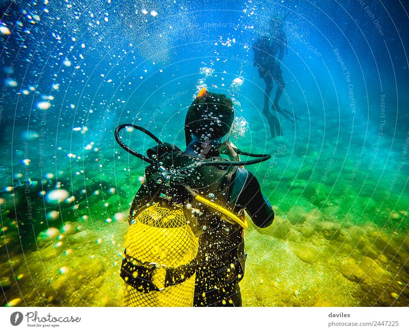 Man in his back with scuba diving equipment exploring the ocean floor. Lifestyle Leisure and hobbies Vacation & Travel Adventure Ocean Sports Aquatics Dive