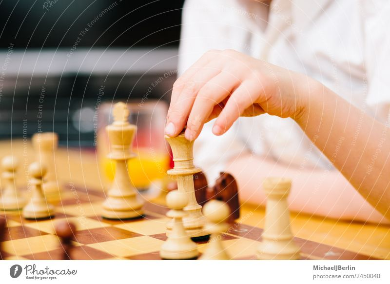 Boy of primary school age plays chess Joy Leisure and hobbies Playing Board game Chess Flat (apartment) Living room Think Boy (child) Colour photo Interior shot