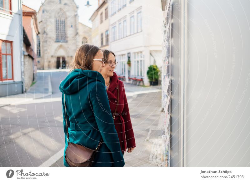 Twins look at shops with postcards Lifestyle Joy luck Human being Feminine Young woman Youth (Young adults) Brothers and sisters Sister 2