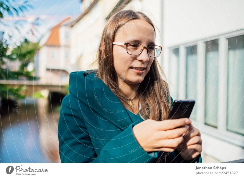 young woman with blue coat is standing at the river and typing in smartphone Lifestyle Style Joy luck Human being Feminine Young woman Youth (Young adults)