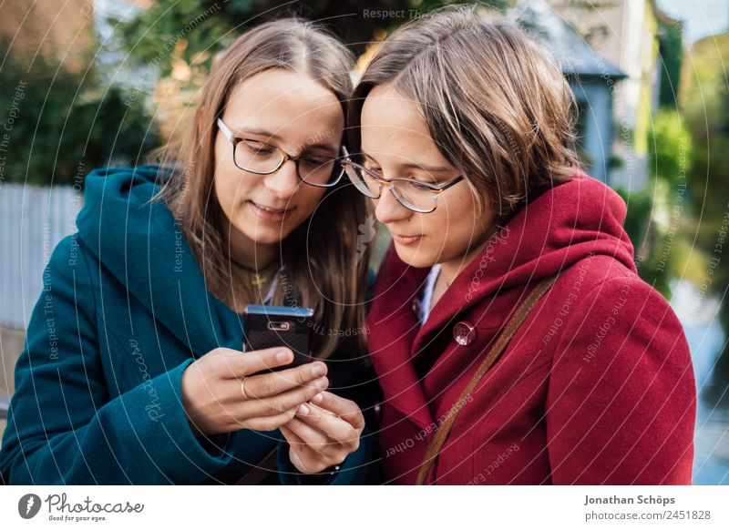 Twin sisters looking at a smartphone together Lifestyle Style Joy luck Human being Feminine Young woman Youth (Young adults) Brothers and sisters Sister 2