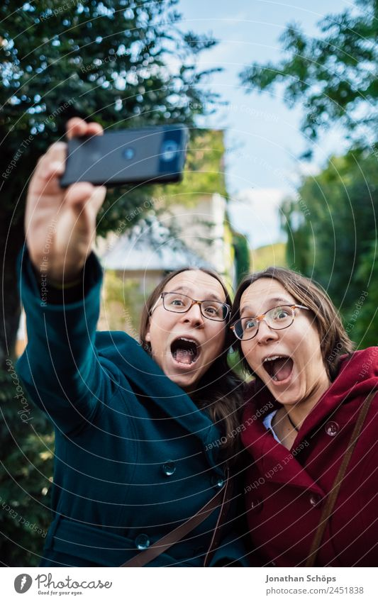 funny twin sisters make a selfie with the smartphone Lifestyle Joy luck Human being Feminine Young woman Youth (Young adults) Brothers and sisters Sister 2
