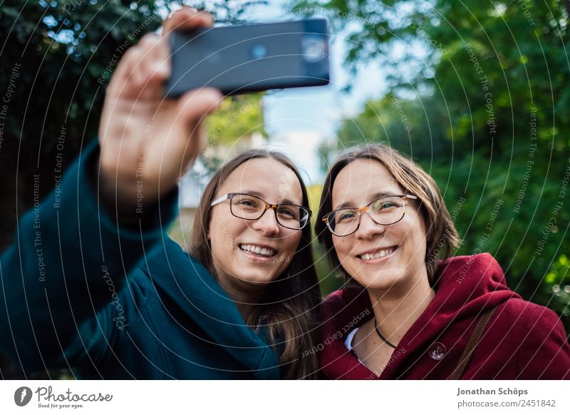 happy twin sisters make a selfie with the smartphone Lifestyle Style Joy luck Human being Feminine Young woman Youth (Young adults) Brothers and sisters Sister