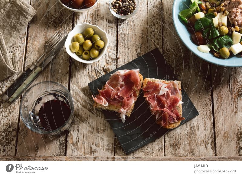 Delicious appetizer of spanish ham and salad Ham Spanish Bread Toast Appetizer cookery Cut Sandwich iberic Pork Lunch Meal Salad Dinner stuffed olives Rustic