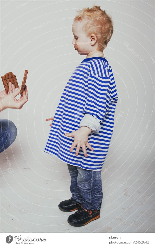 a little boy is offered a chocolate Human being Blue Face Eating Adults Family & Relations Boy (child) Food Fashion Hair and hairstyles Body Infancy Skin