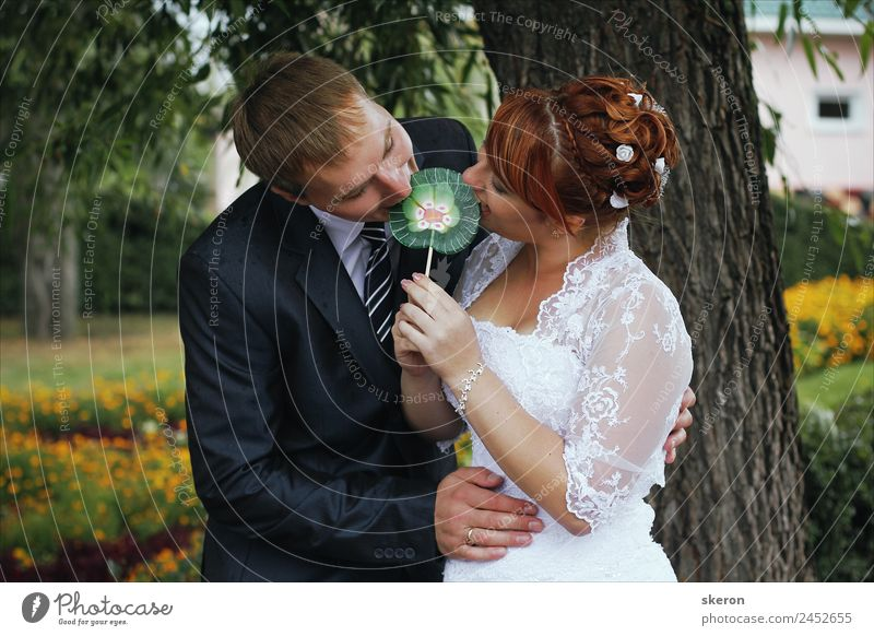 the bride and groom biting a Lollipop Lifestyle Leisure and hobbies Playing Wedding Masculine Feminine Family & Relations Partner Adults 2 Human being