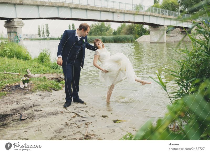 the groom holds a smiling bride who wets her feet in the river Lifestyle Leisure and hobbies Summer Waves Valentine's Day Wedding Masculine Feminine Young woman