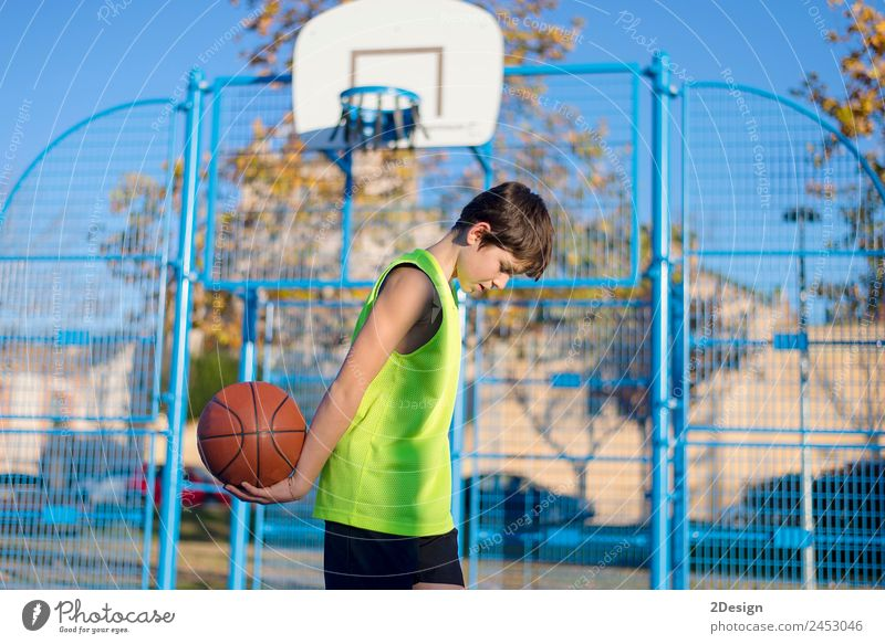 Young basketball player standing on the court Child Human being Youth (Young adults) Man Relaxation Joy Street Adults Lifestyle Yellow Sports Boy (child)