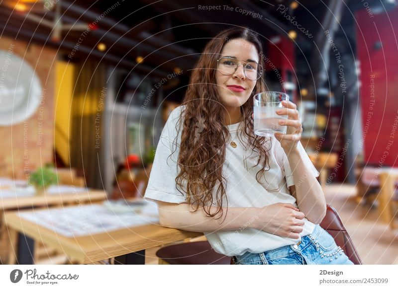 Pretty young woman holding a glass of water Breakfast Beverage Drinking Coffee Lifestyle Happy Beautiful Health care Relaxation Summer Chair Table Restaurant