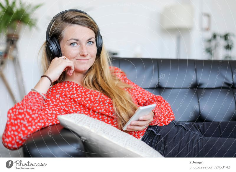 Happy woman listening to music wearing headphones Lifestyle Joy Beautiful Relaxation Calm Leisure and hobbies Playing Sofa Music Telephone PDA Technology