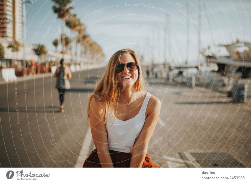 Blonde young woman smiling and laughing while sitting at yacht harbour at sunset. Lifestyle Elegant Joy Leisure and hobbies Vacation & Travel Tourism Summer