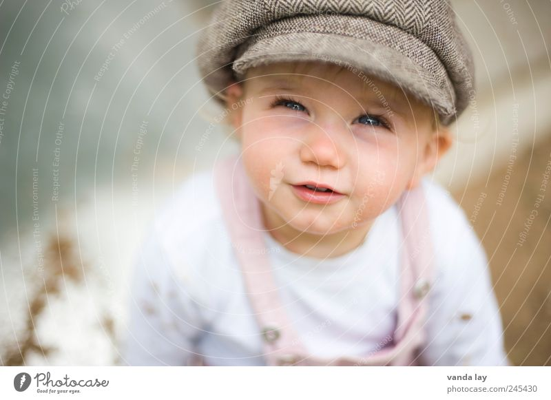 Human being Child Girl Happiness Safety Cool (slang) Infancy Protection Trust Hat Cap Toddler Safety (feeling of) Optimism Children's eyes Overalls