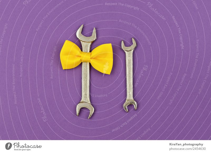 Two wrench large and small with yellow tied bow on violet Man Lifestyle Adults Yellow Love Family & Relations Happy Feasts & Celebrations Copy Space Above