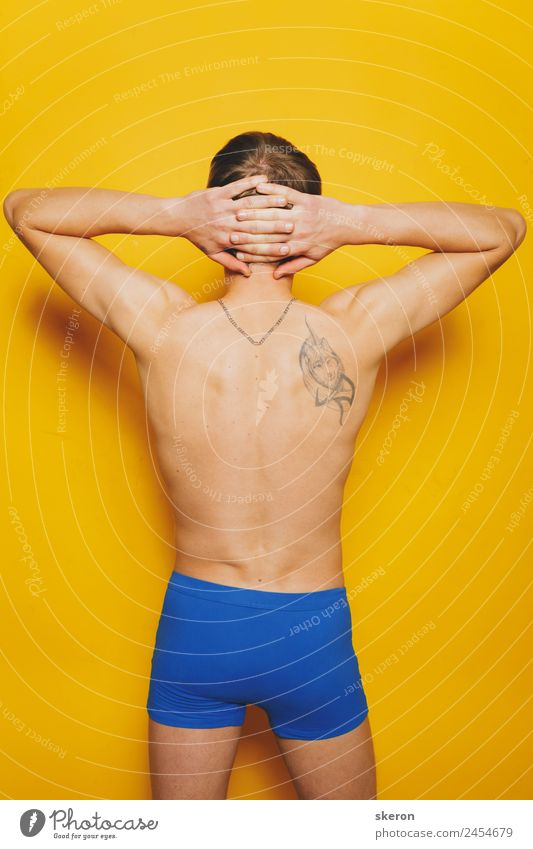 young guy with a tattoo on his back in colored shorts Human being Youth (Young adults) Blue Beautiful Young man Eroticism 18 - 30 years Adults Lifestyle Yellow