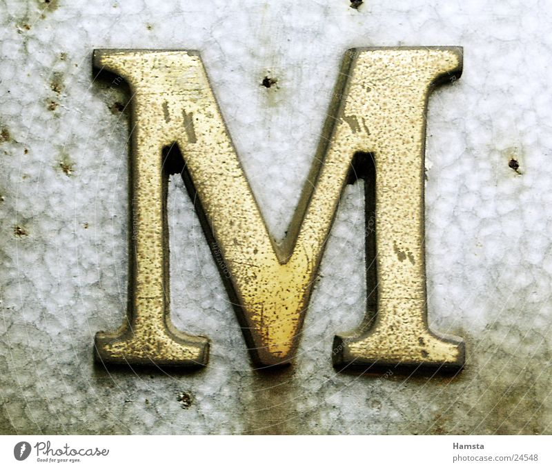 Golden M Letters (alphabet) Serif Obscure Metal Light from side Embossing punching