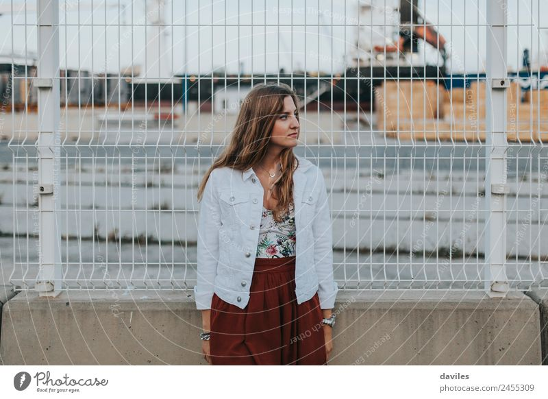 Blonde young woman standing and looking at the right with the industrial port in the background. Lifestyle Beautiful Vacation & Travel Trip Adventure
