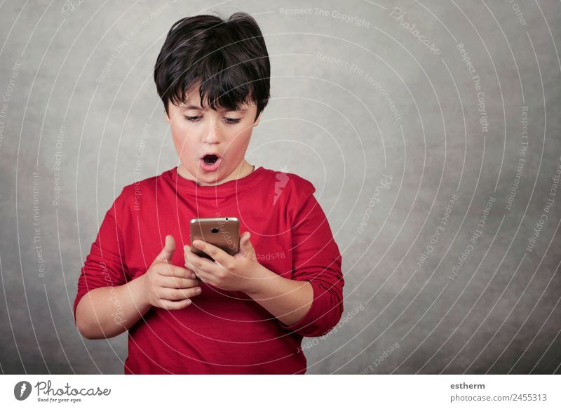 surprised child with a mobile phone on gray background Lifestyle Playing Telephone Cellphone Screen Technology Entertainment electronics Internet Masculine