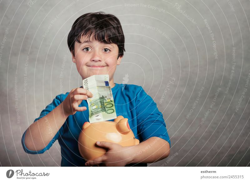 Happy child saving money in a piggy bank Child Human being Joy Lifestyle Boy (child) Business Work and employment Masculine Infancy Smiling Happiness Success