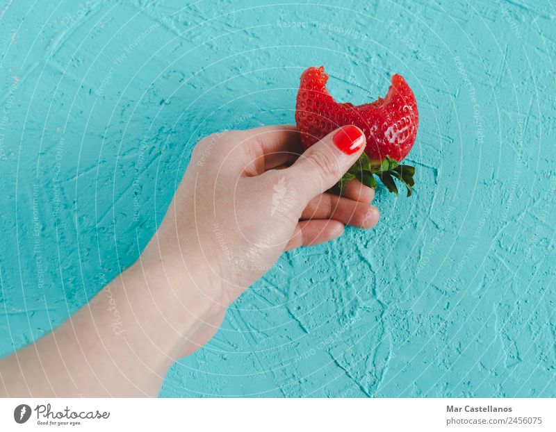 Woman's hand holding a ripe strawberry on blue background. Nature Summer Plant Colour Green Hand Red Eroticism Leaf Joy Eating Adults Healthy Natural Feminine