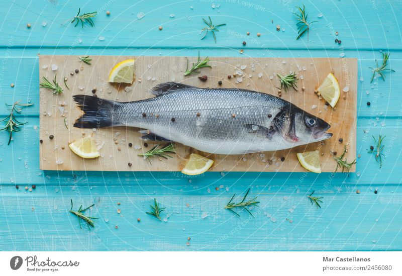 Sea bass with spices on kitchen table and blue wooden background Seafood Herbs and spices Eating Dinner Diet Table Restaurant Animal Wood Write Fresh Delicious