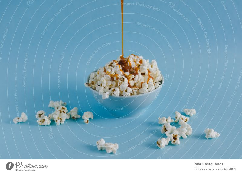 Bowl with popcorn and caramel sauce on blue background Grain Candy Nutrition Eating Leisure and hobbies Table Party Event Feasts & Celebrations Watching TV