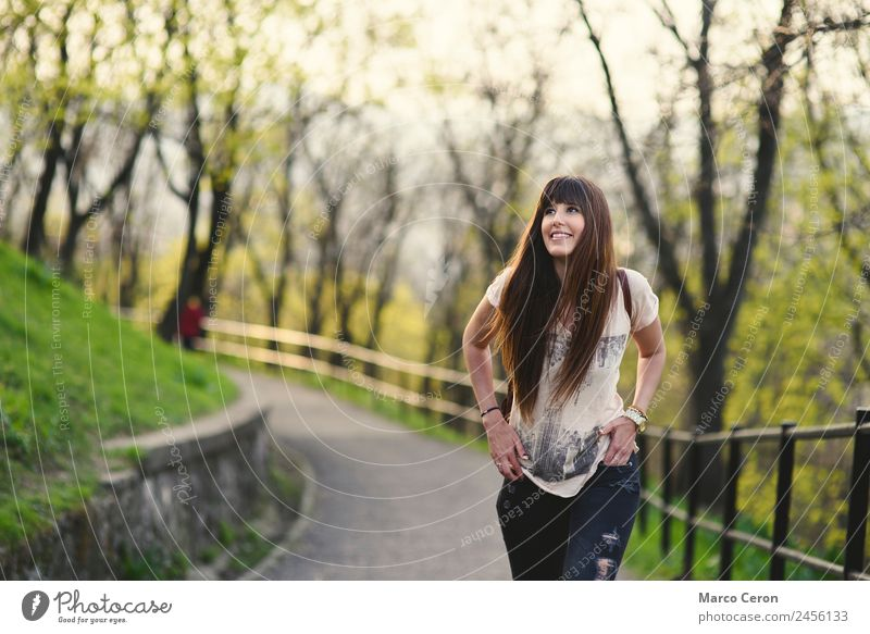 Beautiful girl with long brown hair getting fan and smiling. Woman Human being Nature Vacation & Travel Youth (Young adults) Summer Green Tree Relaxation Joy